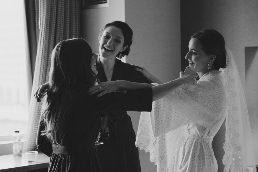 Bride and bridesmaids hugging - Documentary wedding photography