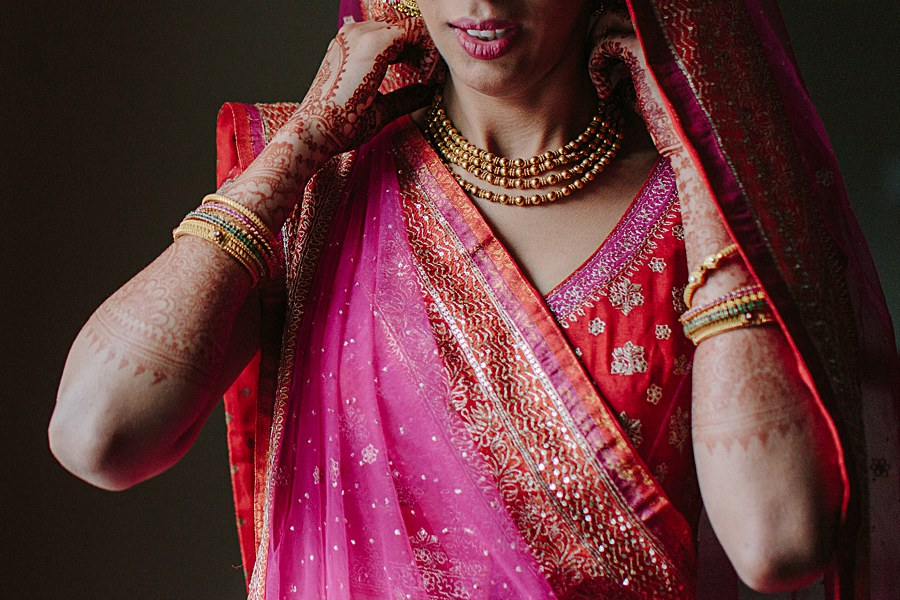 Indian bride getting dressed with traditional indian wedding gown