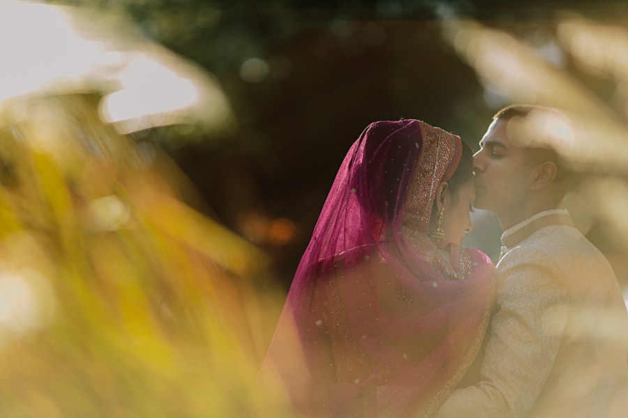 Artistic and romantic bride and groom portrait wearing traditional Indian wedding outfits