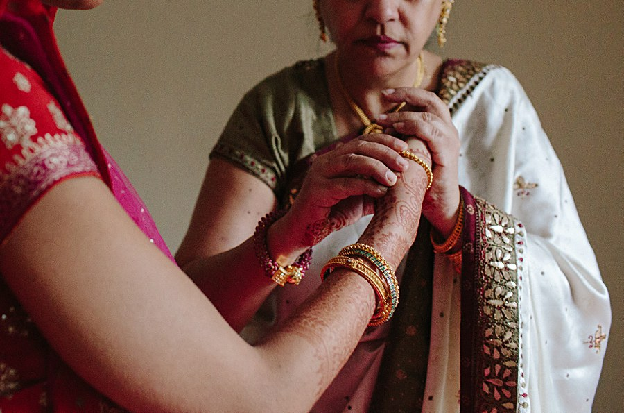 Indian bride putting bracelets on