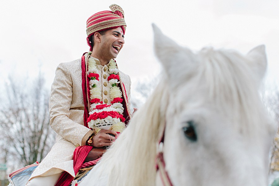 Indian Groom riding his white horse during Baraat